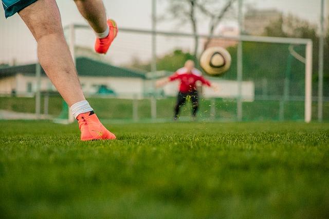Fotbollsspelare skjuter bollen mot mål